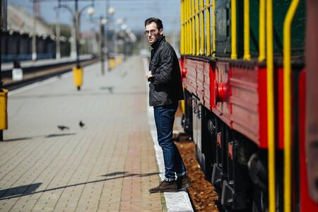 casual men: A man dressed in jeans on the background of the train and the station