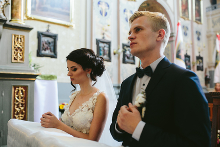 matrimonio feliz: La novia y el novio en la iglesia durante la ceremonia de la boda cristiana.