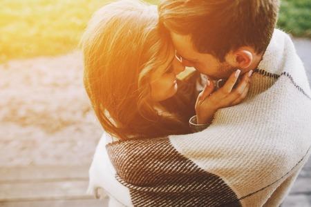 parejas jovenes: Pareja joven en el amor envuelto en tela escocesa de pie y mirando el uno al otro Foto de archivo