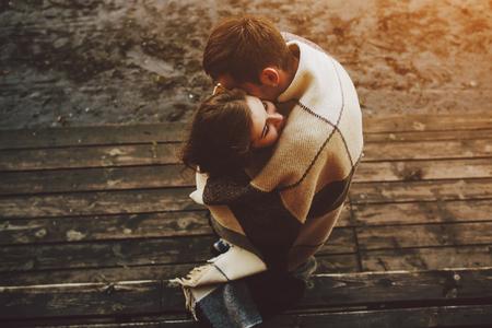 femme romantique: Jeune couple dans l'amour envelopp�e dans plaid debout et embrasser