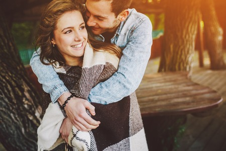 Young couple in love wrapped in plaid standing and embrace