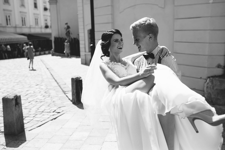 carries: groom carries his bride in his arms through the old town