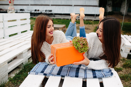 unpack: Two beautiful girls lie on the bench and give each other gifts Stock Photo