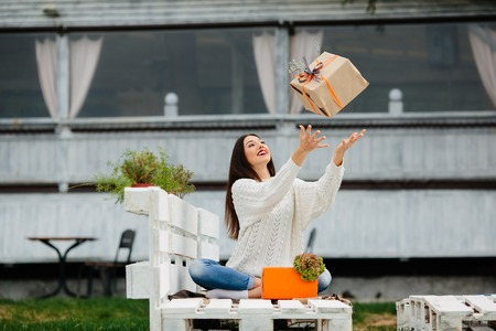 throws: young girl sitting on the bench and throws a gift Stock Photo