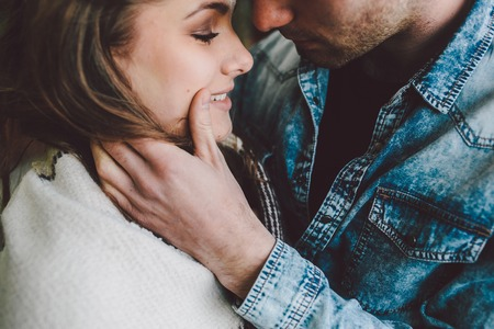 romantic love: Young couple in love wrapped in plaid standing and looking at each other Stock Photo