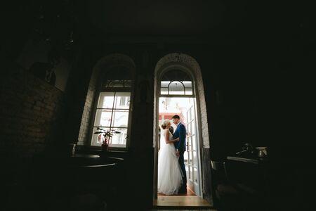 portone: sposa e sposo in giorno delle nozze in posa in un portone