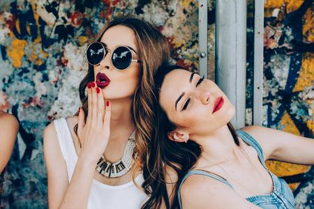 Dos chicas hermosas jóvenes descansan en una parada de autobús Foto de archivo
