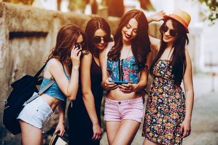 four young beautiful girls on the street looking at the photos on a smartphone