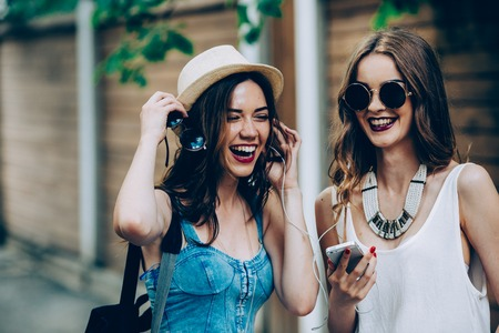 Two young beautiful girls are walking through the city and listen to music Imagens