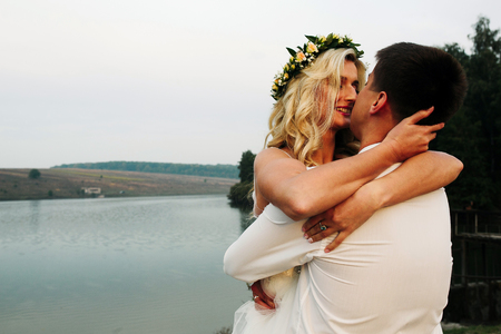 bride in a arms of the groom, outdoors