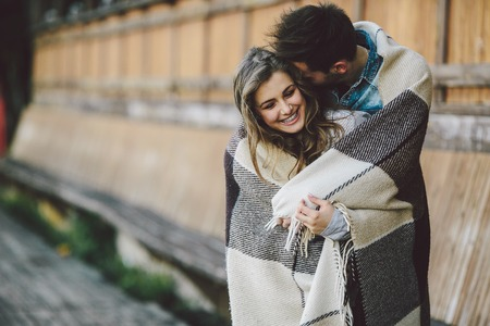 Young couple in love wrapped in plaid standing and looking at each other Banque d'images