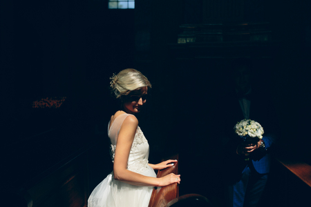bride and groom sitting on a bench in a dark room illuminated by light