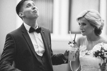 Happy young couple drinking ice coffee through straw on wedding-day outdoors
