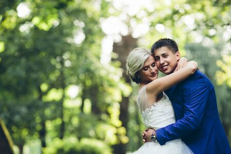 romantic man: Beautiful wedding couple hugging in the park at the camera, close view