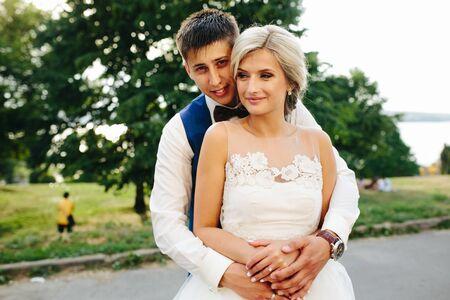 marido y mujer: Pares de la boda hermosa que abraza en el parque a la c�mara, vista de cerca Foto de archivo