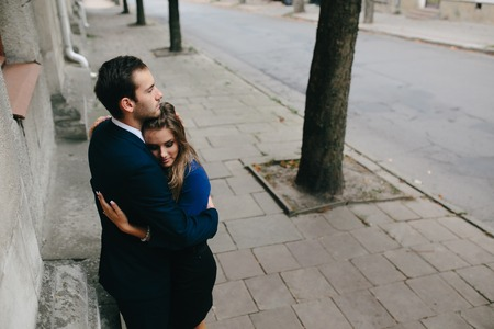 two boys: girl in the arms of her boyfriend on the street