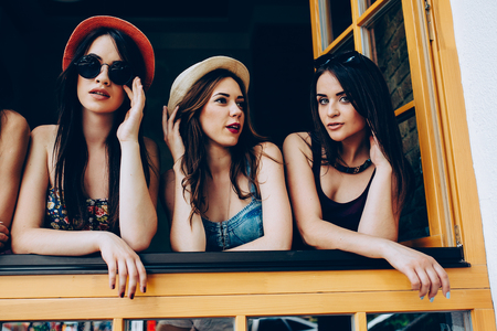 young caucasian: Three beautiful young girls look out from the window