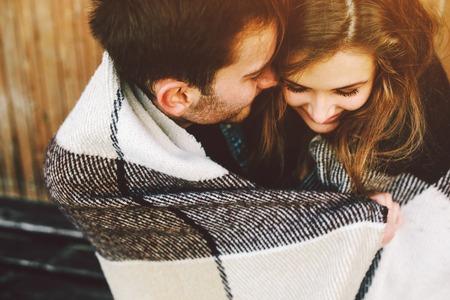 Joven pareja de enamorados envuelta en sesión de tela escocesa y divertirse