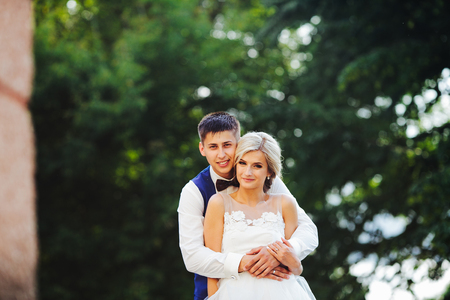 femme romantique: Beautiful wedding couple hugging in the park at the camera, close view