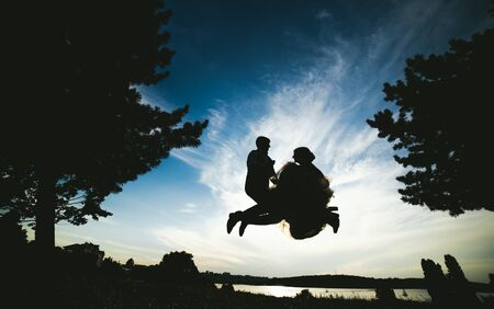 wife and husband: groom and bride jumping against the beautiful sky, silhouettes