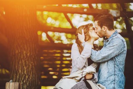 romantic couples: Young couple in love wrapped in plaid standing and kissing Stock Photo
