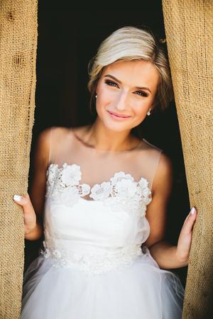 Smiling schöne Braut in den traditionellen weißen Brautkleid