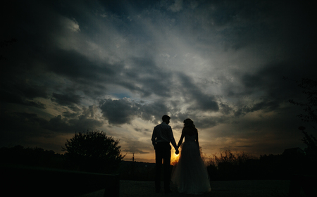Silhouette of  wedding couple in field. Bride and groom together.