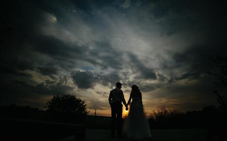 Silueta de los pares de la boda en el campo. La novia y el novio juntos.