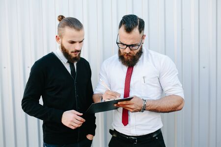 businessman signing documents: Two bearded businessman signing documents in the street