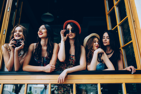 look out: five beautiful young girls look out from the window Stock Photo