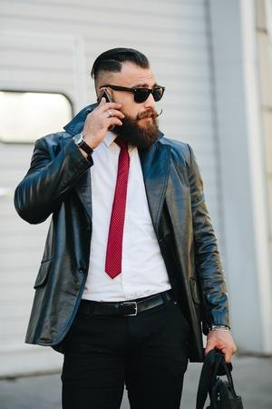apuesto hombre en un traje posando para la cámara en la calle Foto de archivo