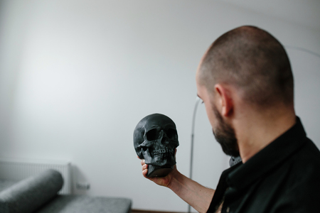 death head holding: handsome, bearded man holding a black skull Stock Photo