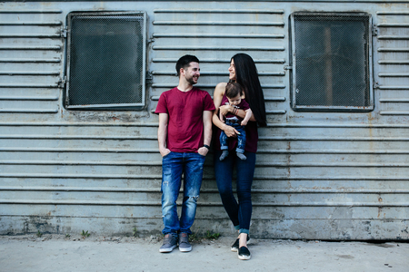 lifestile: young beautiful family with child posing on the building background