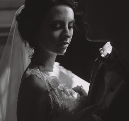 dimly: Bride and groom posing in the dimly lit room