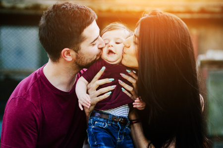 the child laughing: Young family with child posing on the background of an abandoned building