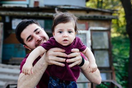 Jeune famille avec enfant posant sur le fond d'un bâtiment abandonné Banque d'images
