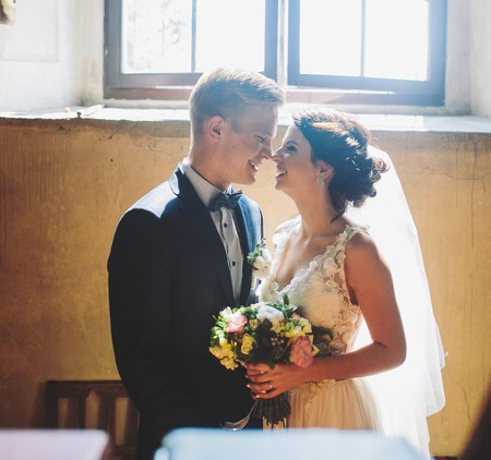 Bride and groom posing on the background of a large window Stock Photo