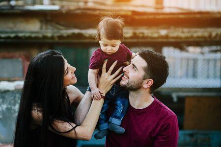 Familia joven con niño posando en el fondo de un edificio abandonado Foto de archivo - 63185718