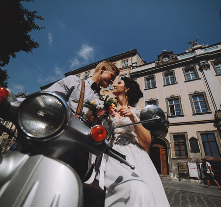 motor scooter: bride and groom posing on a vintage motor scooter