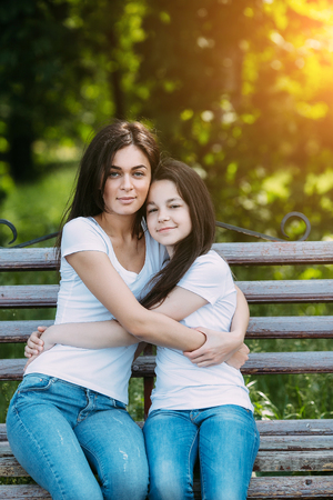 mother on bench: Mother and daughter sitting on a bench in the park
