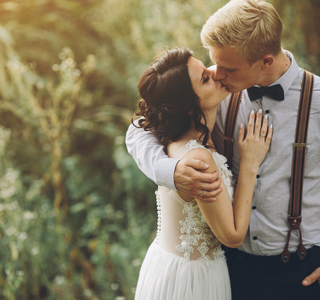 bride and groom kissing in the forest Stock Photo