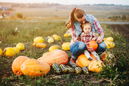 Mother and daughter sitting on pumpkins, Halloween eve Banque d'images
