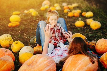 mother and daughter lie between pumpkins on the field, Halloween eve