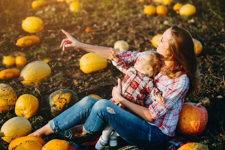 mother playing with her daughter on a field with pumpkins, Halloween eve Stock Photo