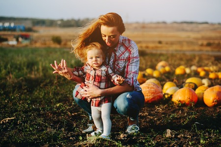 mother teaching her daughter to walk on the field with pumpkins, Halloween eve