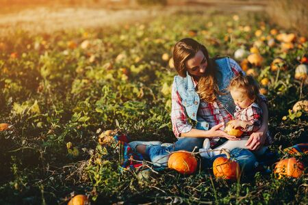 mother and daughter on a field with pumpkins, Halloween eve Banque d'images