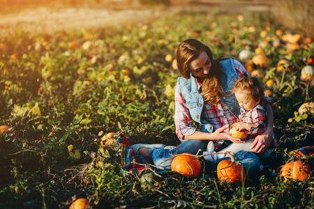 madre e hija en un campo con calabazas, víspera de Halloween Foto de archivo