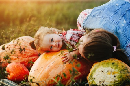 daughter lying on a pumpkin, and her mother standing beside, Halloween eve Stock Photo