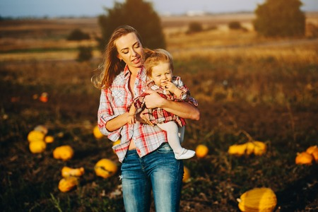 mother and daughter on a field with pumpkins, Halloween eve Stock Photo