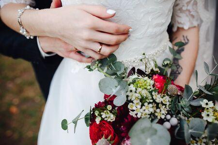 Novia que sostiene el ramo de la boda en sus manos, opinión del primer